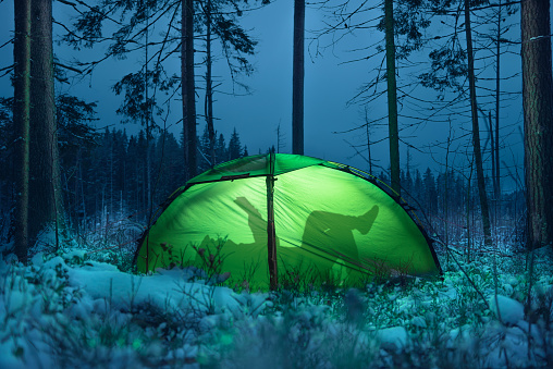 Silhouette of a man in a tent. He reads a book. Winter forest
