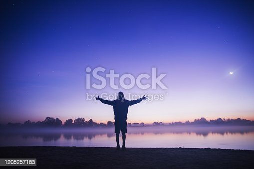Silhouette of a man in the darkness. Freedom concept. Man rise hands. Night photography. Fog over river. Mysterious anonymous figure. Misty sunrise.  Ghost figure. Silhouette of person. Dark shadow.