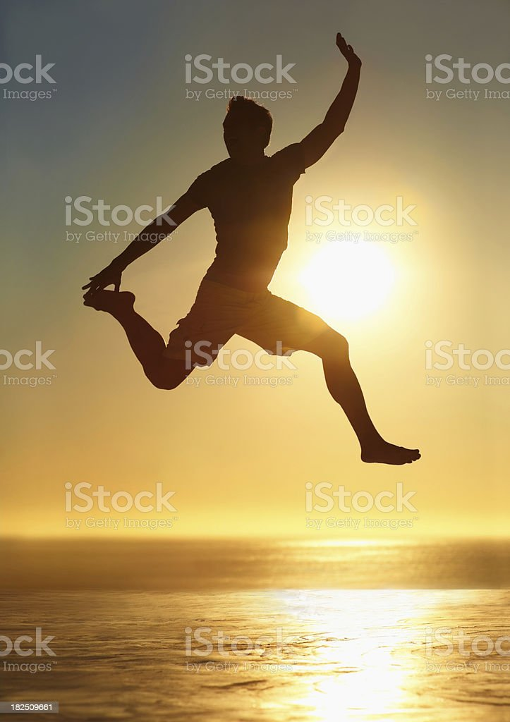 Silhouette of a man jumping in mid air against sunset royalty-free stock photo