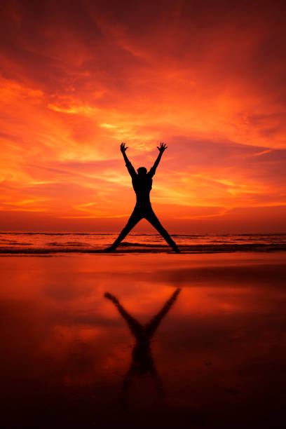 Silhouette of a man Jumping in the air on a beach stock photo