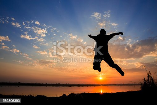istock Silhouette of a man jumping over sunset background 539306393
