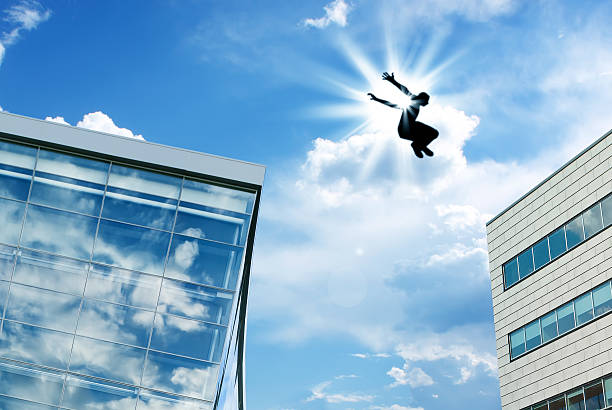 silhouette of a man leaping off building - daredevil stock pictures, royalty-free photos & images