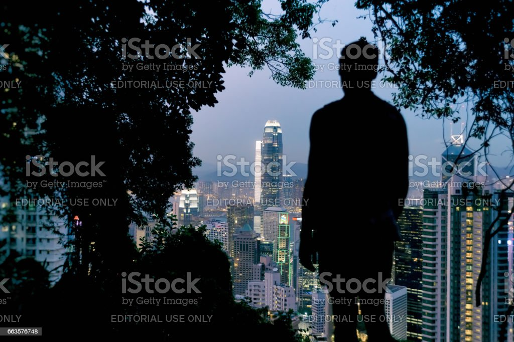 Silhouette of a man looking at Hong Kong Skyline from Victoria Peak stock photo