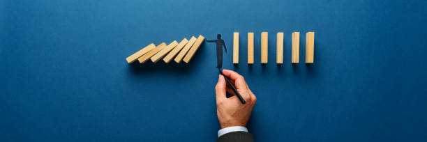 Silhouette of a man making a stop gesture to prevent wooden dominos from collapsing stock photo