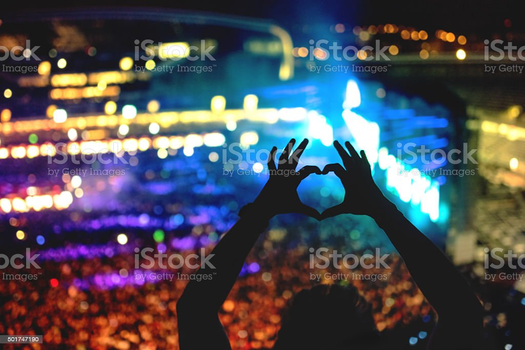 Silhouette of a man making heart from hand gestures stock photo