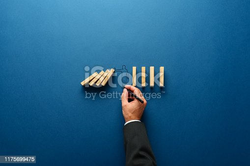 Businessman drawing silhouette of a man making stop gesture to stop dominos from falling in a conceptual image. Over navy blue background with copy space.
