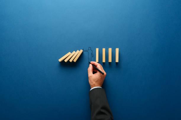 Silhouette eines Mannes, der Stopp-Geste macht, um Dominos vor dem Fallen zu bewahren – Foto