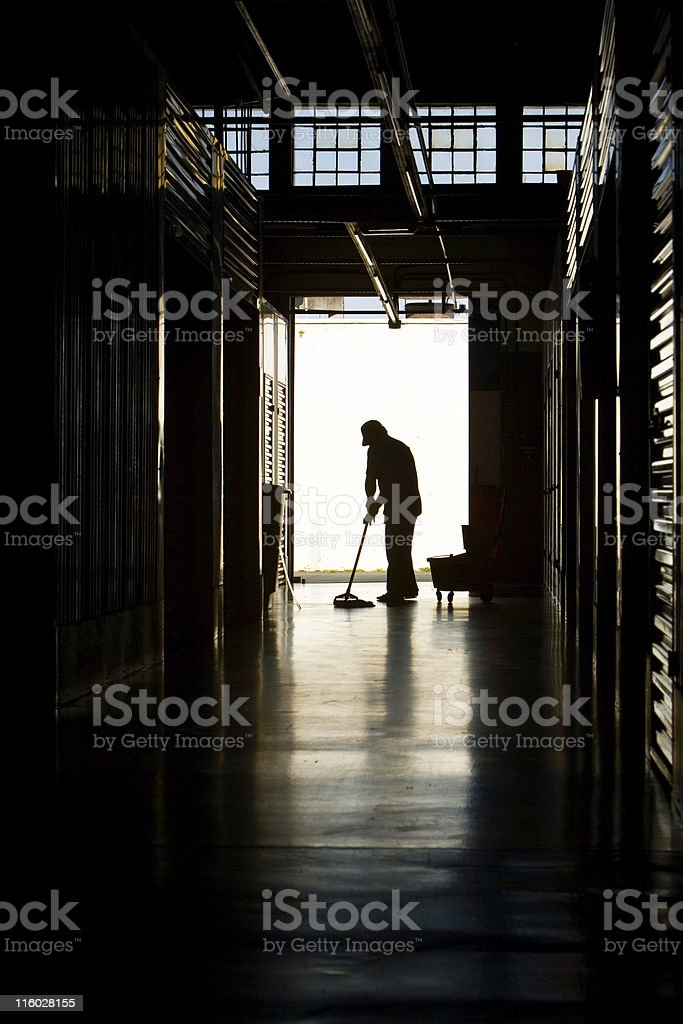 Silhouette of a man mopping a floor in the evening stock photo