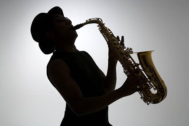 silhouette eines saxophonist - altsaxophon stock-fotos und bilder