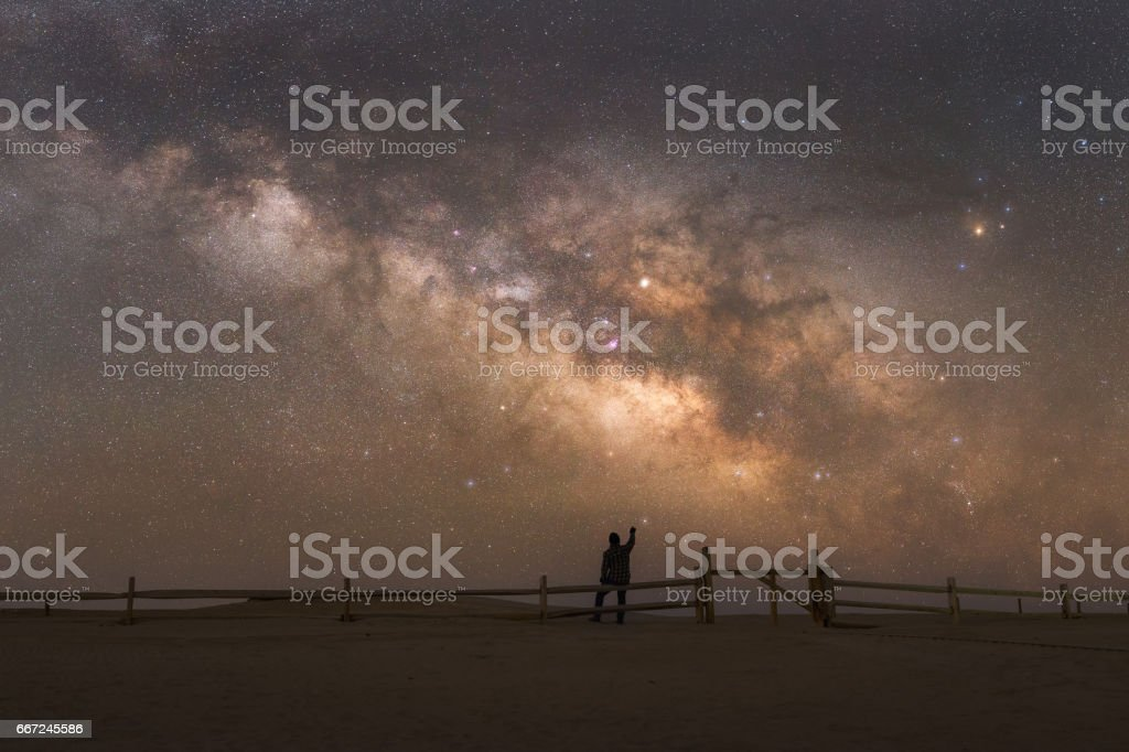 Silhouette of a man pointing to the Milky Way Galaxy stock photo