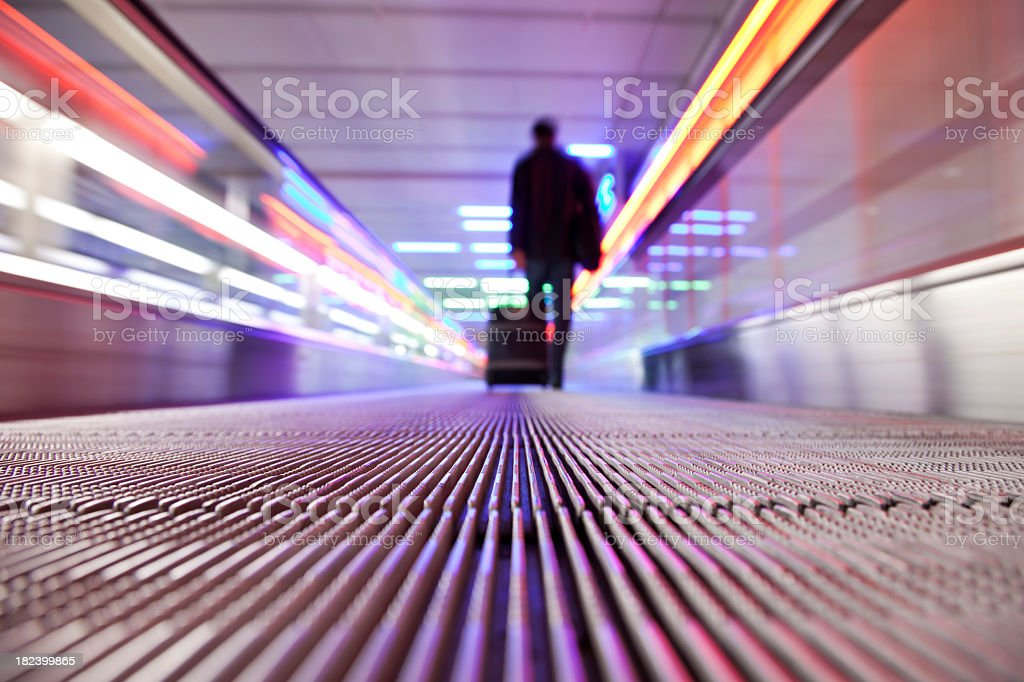 A silhouette of a man pulling his trolley in an escalator royalty-free stock photo