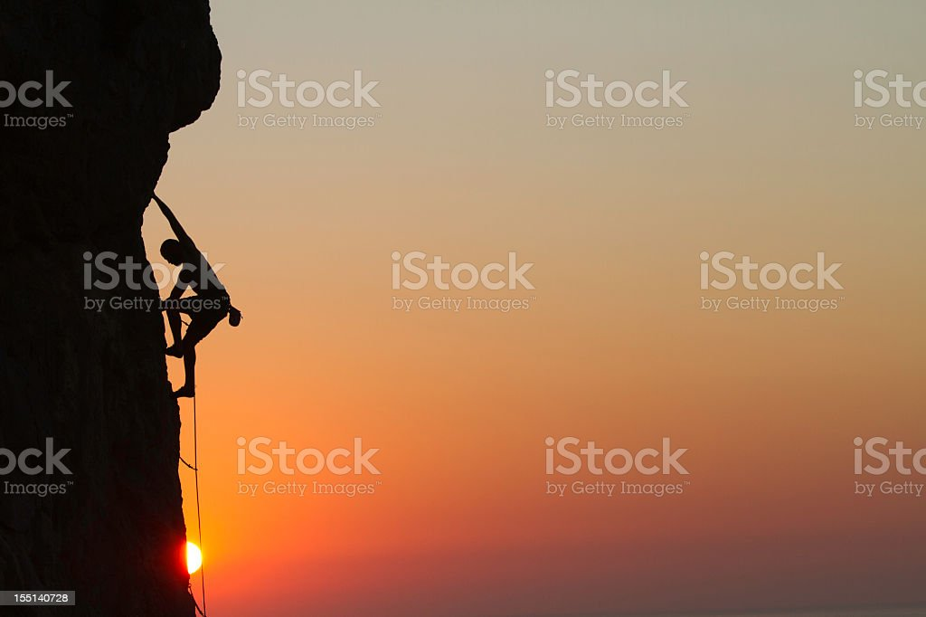 Silhouette of a man rock climbing at sunset royalty-free stock photo