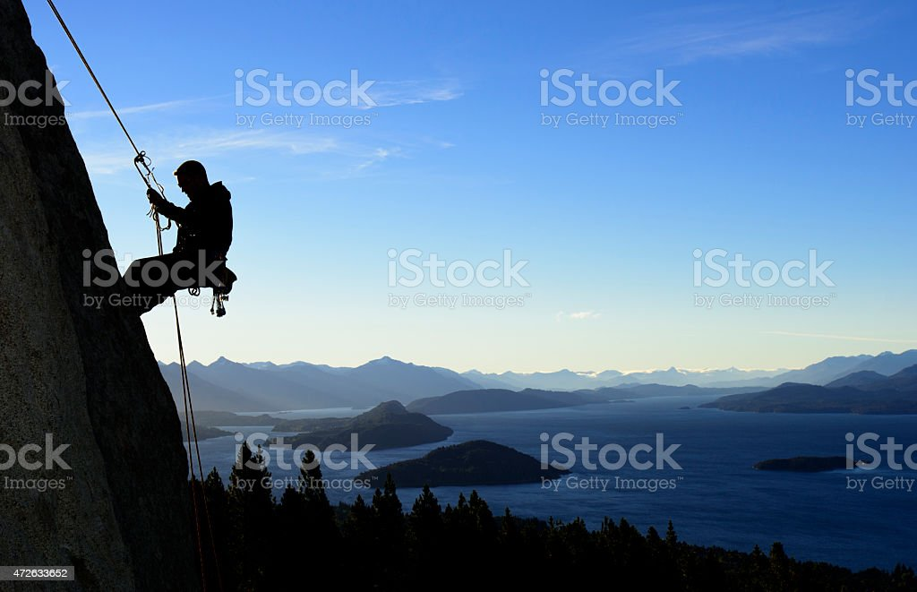 A silhouette of a man rock climbing in Patagonia stock photo