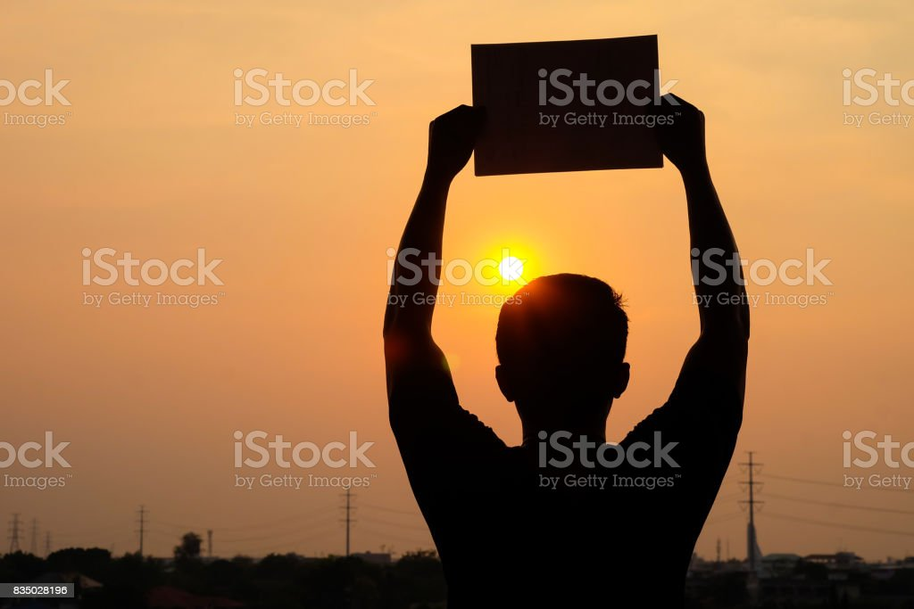 silhouette of a man shows blank sign board on a sunset background. Concepts, claims, announcements, or wants to be seen. stock photo