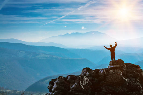Silhouette of a Man standing on a stone cliff, success and victory in the mountains stock photo