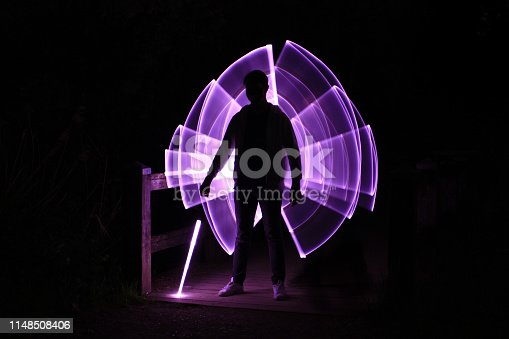 istock Silhouette of a man standing with a lightsaber 1148508406