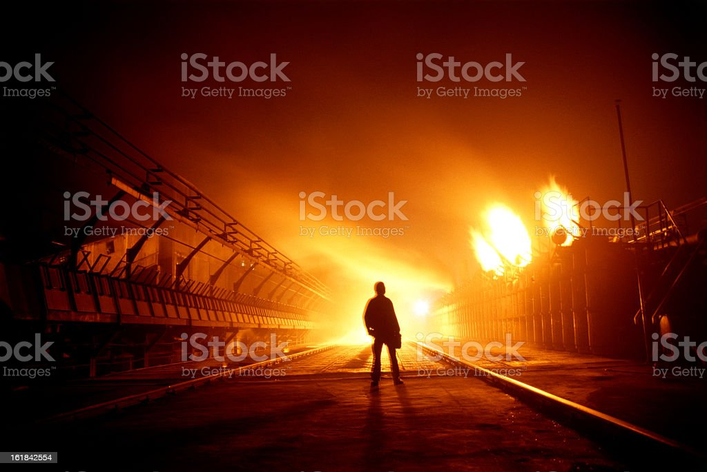 Silhouette of a man standing with burning buildings around stock photo