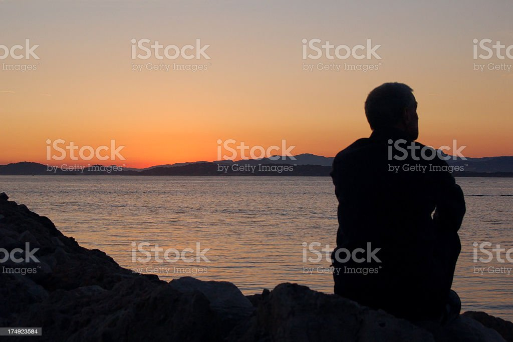 Silhouette of a man staring at a sunset royalty-free stock photo