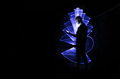 Boy using technology. Abstract shape at lightpainting with a light saber. Face illuminated by screen.