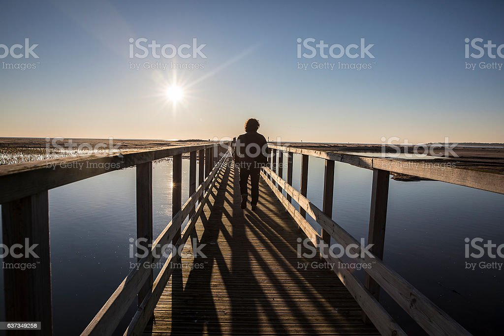 silhouette of a man walking on a pontoon at sunset stock photo