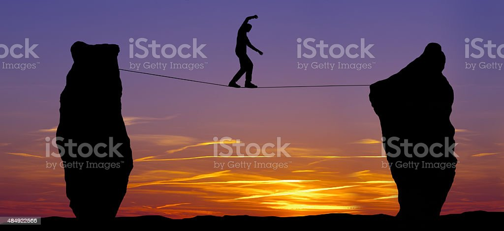 Silhouette of a man walking on the tightrope stock photo
