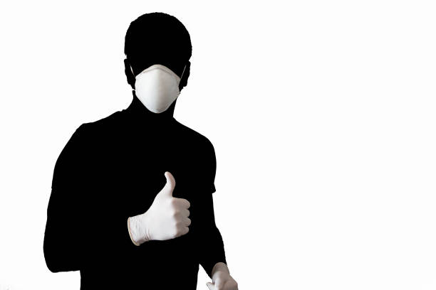 Silhouette of a man wearing a face mask and gloves with thumb up on white background stock photo