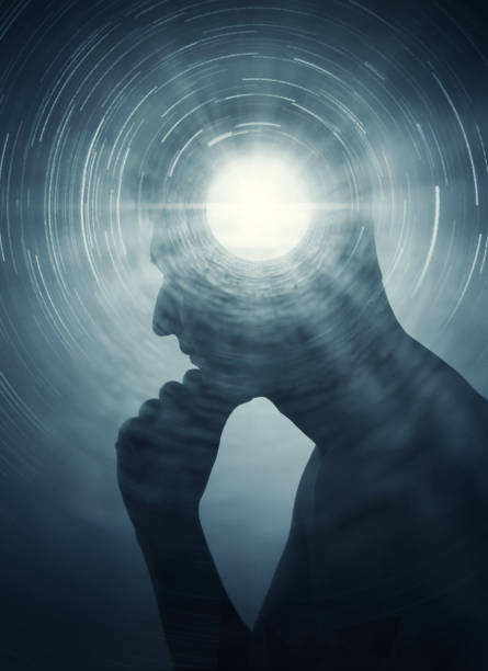 A silhouette of a man with rays of light emanating from the brain as a symbol of the power of thinking. stock photo