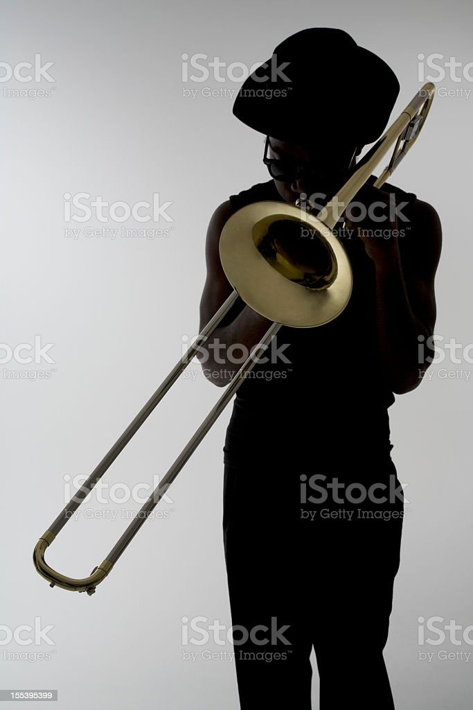 Silhouette of a man with sunglasses playing the trombone stock photo