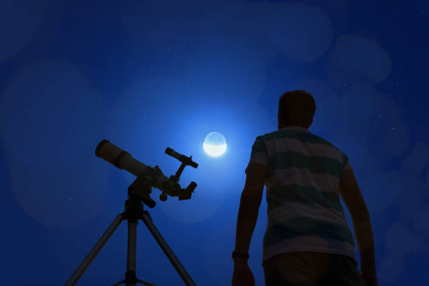 Silhouette of a man with telescope, Moon and stars. My astronomy work. stock photo