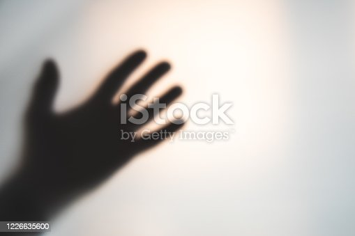 Silhouette of a man's hand waiving through opaque plastic sheeting of a quarantined area.  Belfast, Northern Ireland.