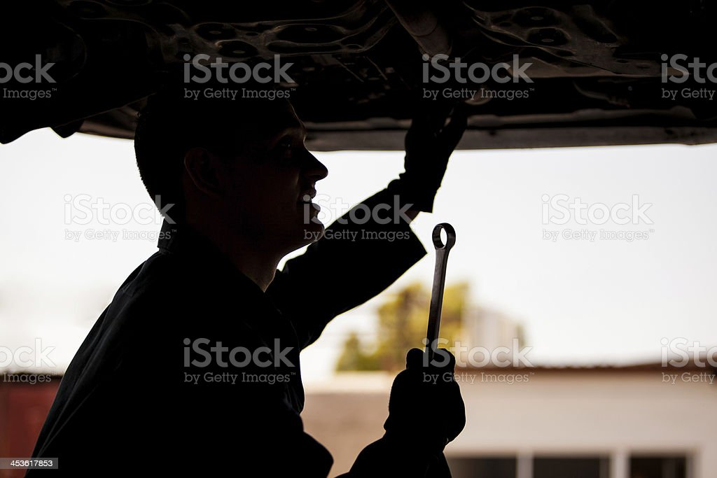 Silhouette of a mechanic at work stock photo