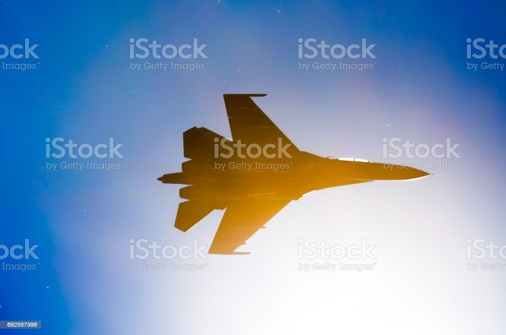 Silhouette of a military fighter sun lights blue sky. stock photo