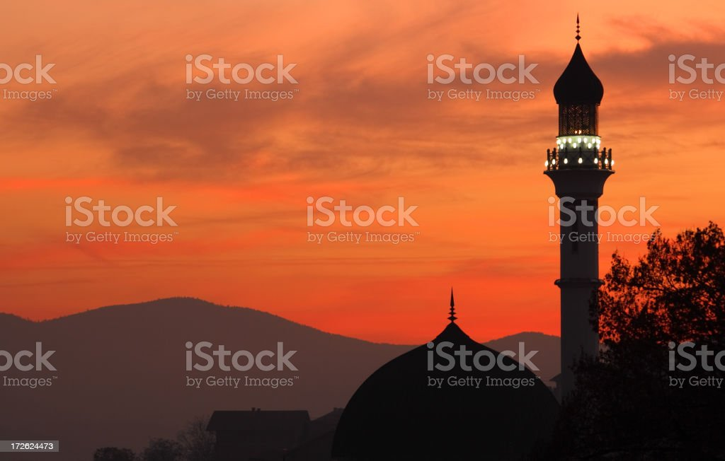 Silhouette of a mosque at dusk with an orange sky stock photo