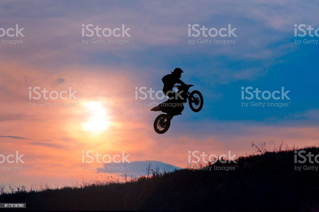 Silhouette of a motorbike rider stunting on sunset stock photo