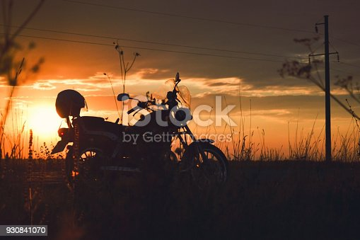 istock Silhouette of a motorcycle on the road at sunset 930841070