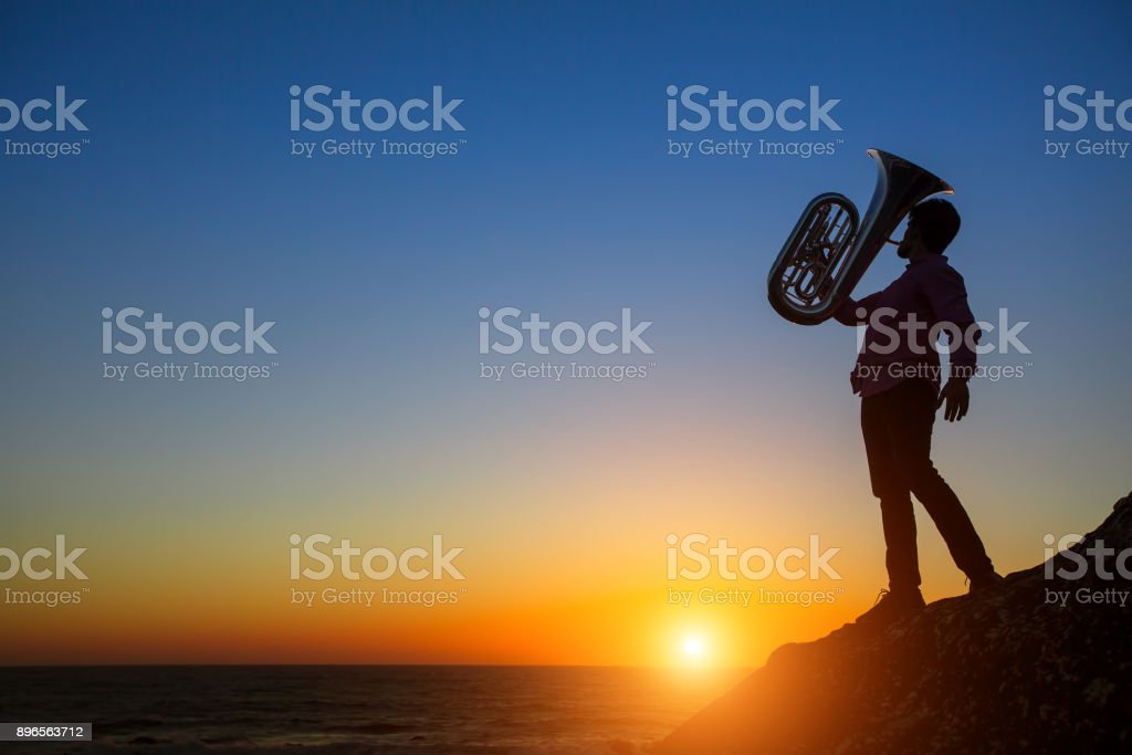 Silhouette of a musician play Tuba at sunset on sea shore. stock photo