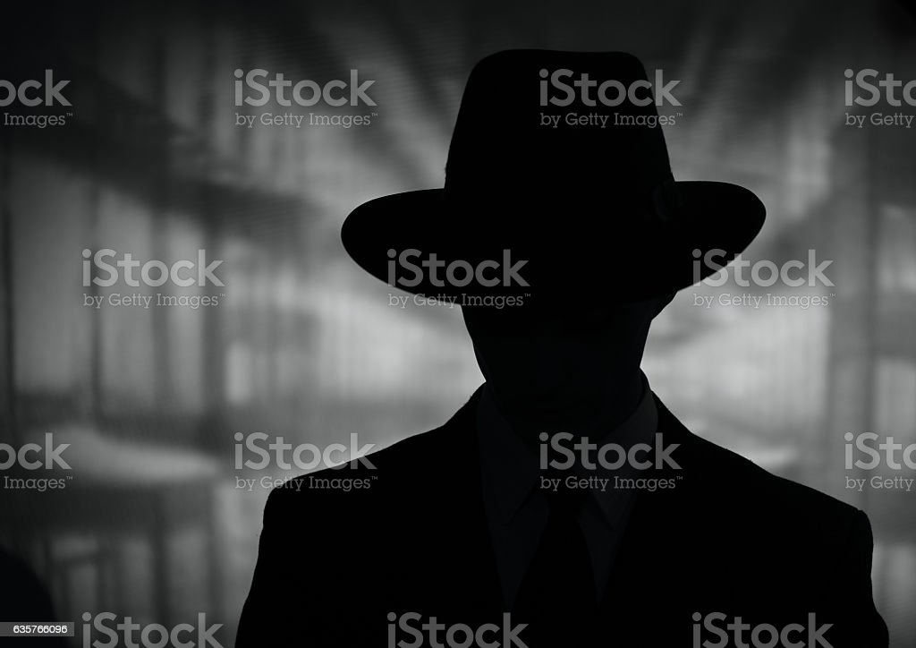 Silhouette of a mysterious man in a hat stock photo