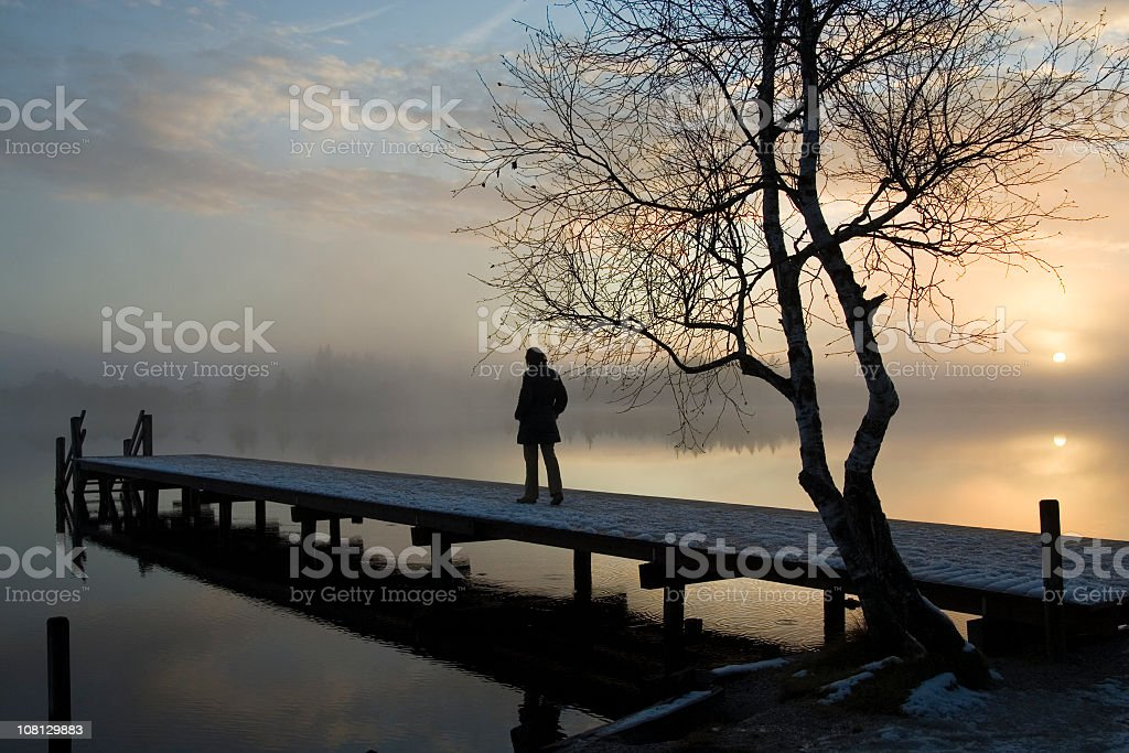 Silhouette of a person alone on a dock royalty-free stock photo