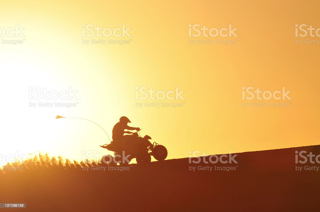 Silhouette of a person riding a quad bike at sunset stock photo