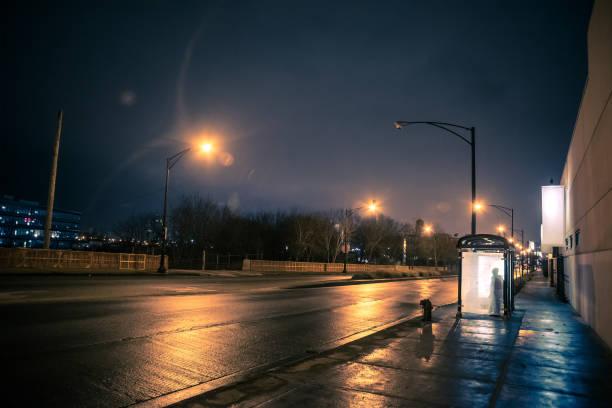 silhouet van een persoon te wachten in een bushalte van de stad bij nacht - bushalte stockfoto's en -beelden
