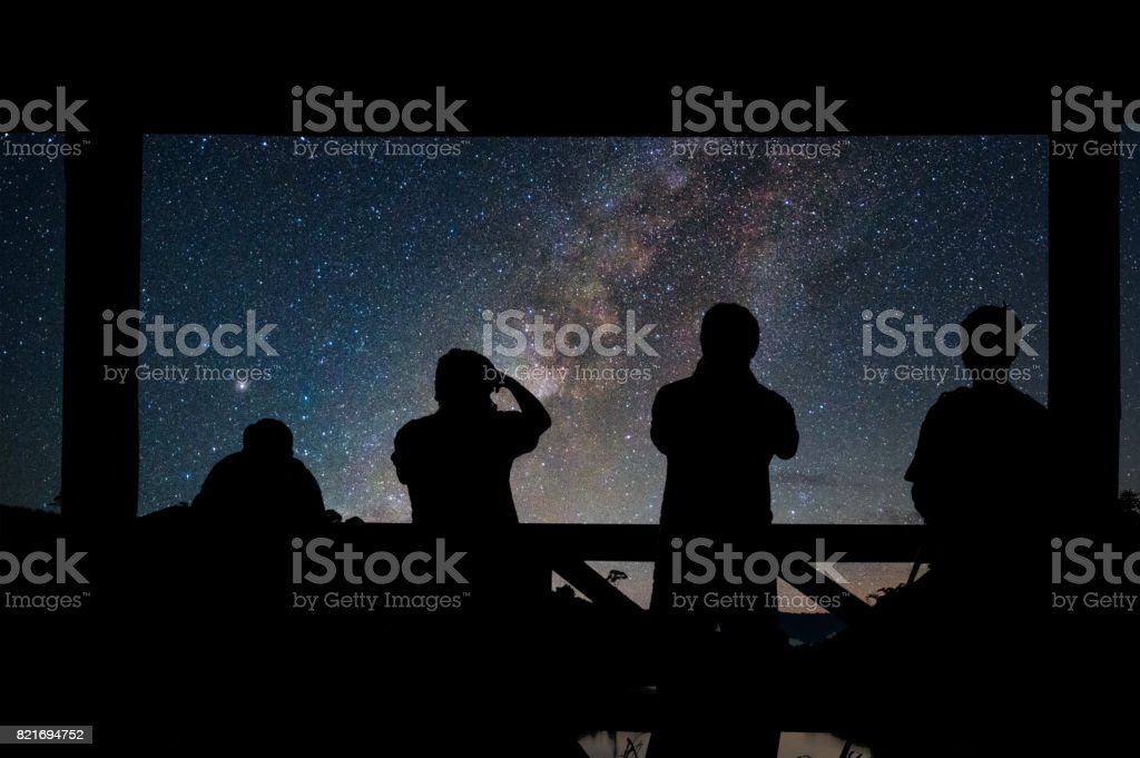 Silhouette of a photographers group who shoots the Landscape of Milky way over reservoir with mountain and deep forest at night sky stock photo
