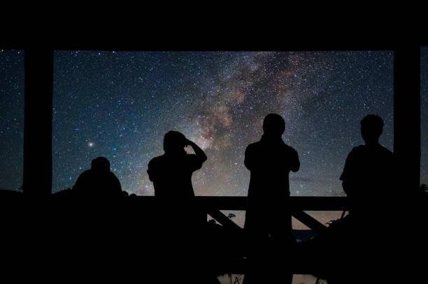 silhouette d'un groupe de photographes qui tire le paysage de milky way sur le réservoir avec la montagne et la forêt profonde au ciel nocturne - astronomie photos et images de collection