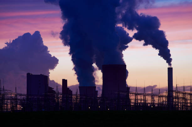 Silhouette of a power plant spilling steam into the sky stock photo