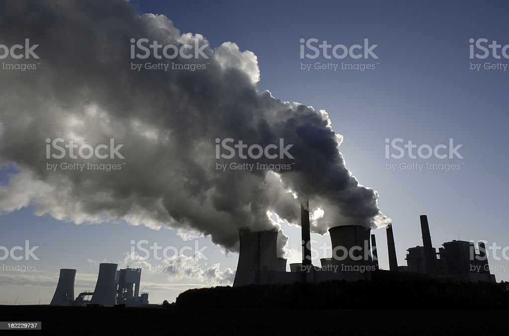 Silhouette of a power plant with pollution stock photo