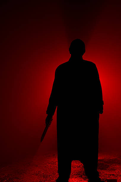 Silhouette of a psycho killer with a knife on red stock photo