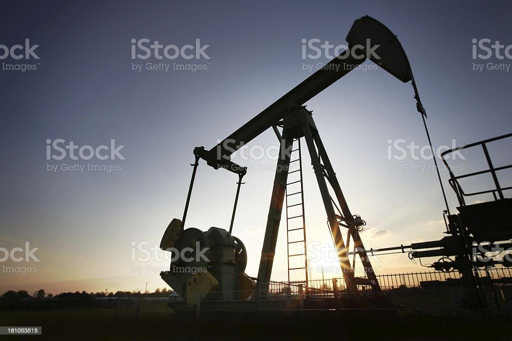 Silhouette of a pumpjack at sunset royalty-free stock photo