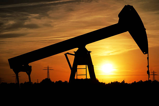 Silhouette of a pumpjack at sunset stock photo