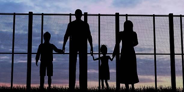 Silhouette of a refugees family with children - foto de acervo