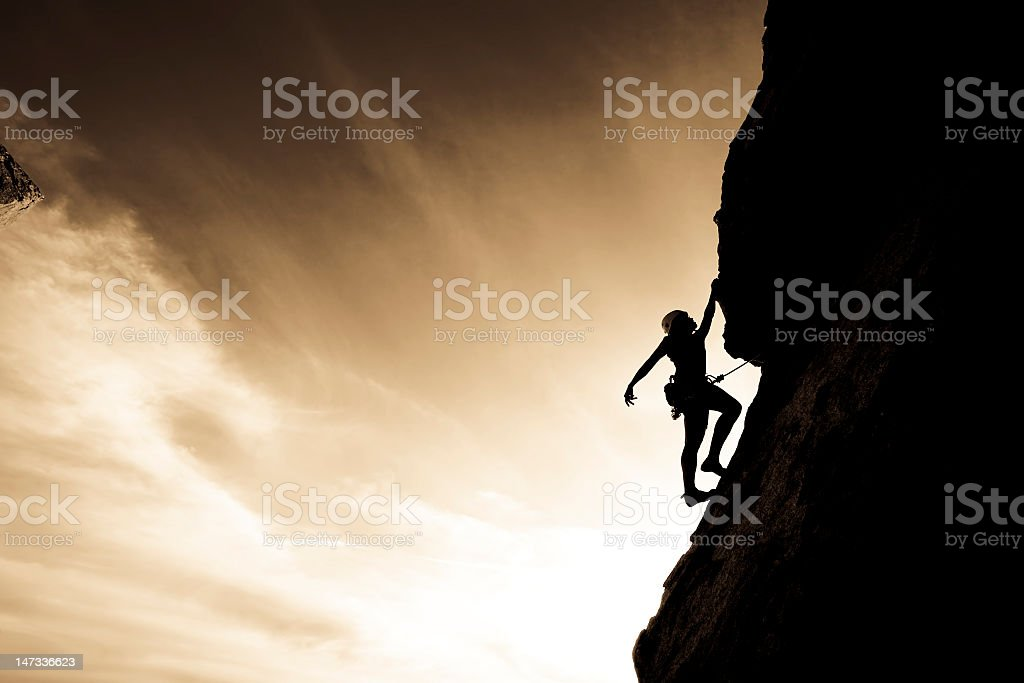 Silhouette of a rock climber clinging to a cliff royalty-free stock photo