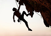 Silhouette of a rock climber hanging off cliff with one arm